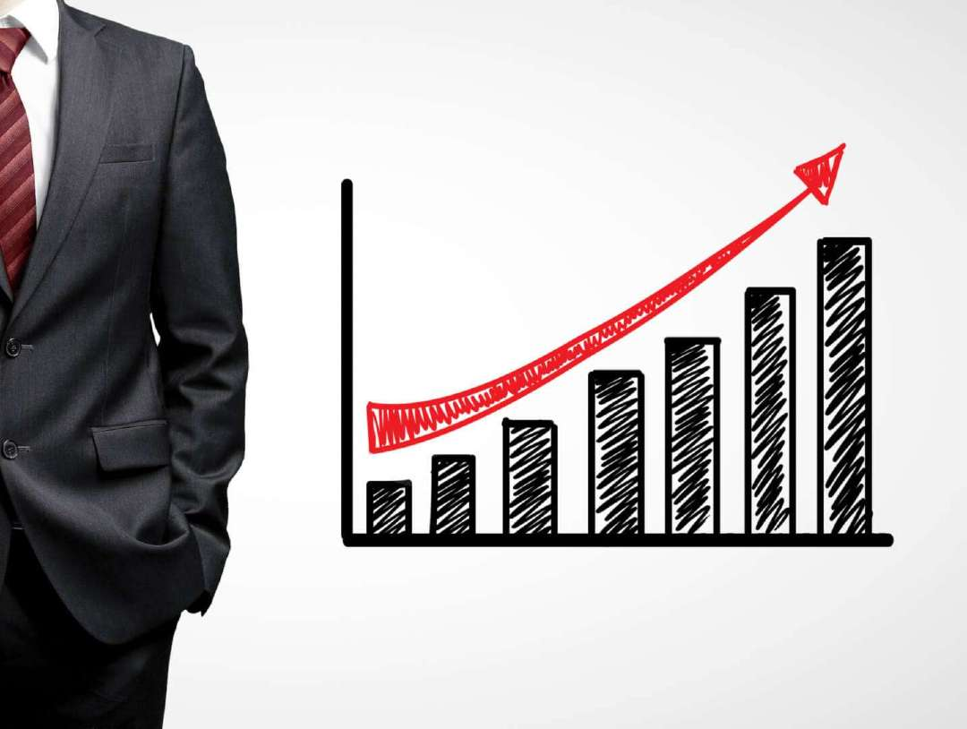 person wearing suit standing next to a bar chart indicating growth over time
